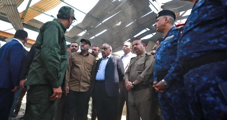ابو الولاء الولائي ورائد الفرطوسي يستقبلان عبد المهدي بمكان انفجار معسكر سكانيا في بغداد